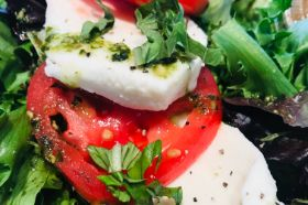Fresh mozzarella, tomato and fresh basil drizzled with pesto over mesclun greens and served with balsamic