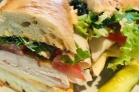 Boars Head Chipotle Turkey with provolone, tomato, chipotle bacon mayo and mesclun greens on baguette